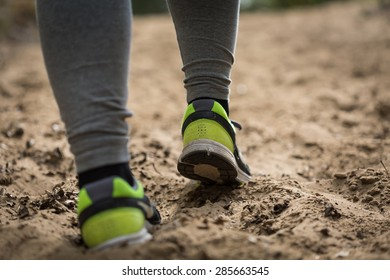 Close-up of woman runner's legs jogging outdoors