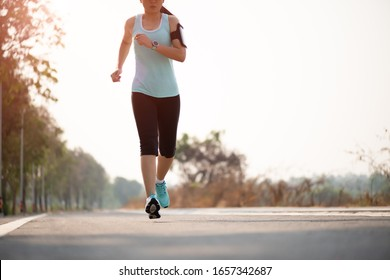 Closeup woman running towards on the road side. Step, run and outdoor exercise activities concept.