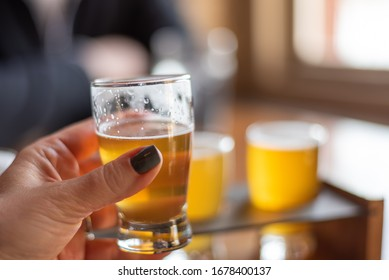 Closeup of a woman sampling beer from a flight at a local brewery
