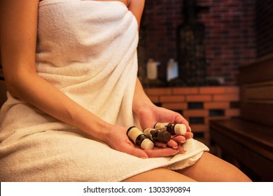 Closeup of woman in the sauna with aromatic oil bottle for bath
