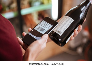 Closeup of woman scanning bar code with mobile phone on wine bottle in grocery store