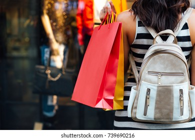 Closeup of woman with shopping bags looking at a boutique window shop