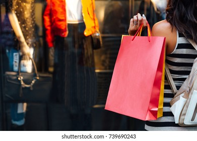 Closeup of woman with shopping bags looking at a boutique window shop with copy space