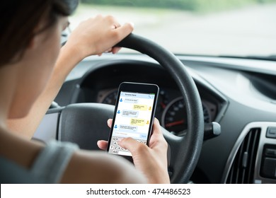 Close-up Of Woman Sitting Inside Car Typing Text Message On Mobile Phone