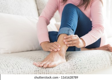 Closeup woman sitting on sofa holds her ankle injury, feeling pain. Health care and medical concept.
