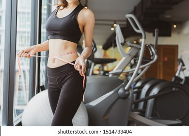 Closeup woman slim athlete using body fat measurement and waist size with waist line after workout at fitness gym healthy lifestyle weightloss happy in goal.
