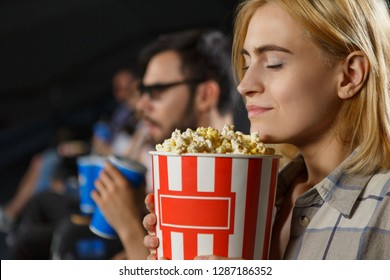 Closeup of woman smelling tasty popcorn during watching film at cinema