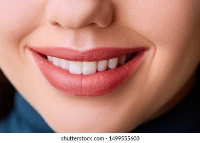 Closeup Woman smile. Teeth whitening. Dental care. Restoration concept