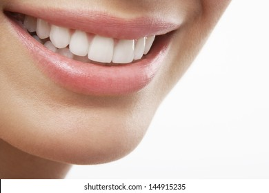 Closeup of woman smiling with prefect white teeth on white background