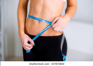 Close-up of a woman in sportswear measuring her waist