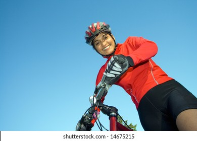 Close-up of woman standing next to bicycle, looking down and smiling. Wearing sports gear and helmet. Horizontally framed shot.