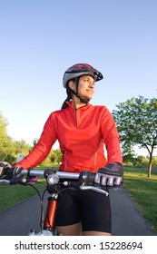 Close-up of woman standing next to bicycle and smiling in the park. Wearing sports gear and helmet. Vertically framed shot.