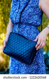 Close-up of a woman standing on the street in a blue dress and holding a blue leather bag on the background of nature.