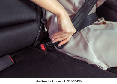 Close-up woman in strict pink suit fastens her seat belt on passenger seat. Safety on road driving car. Unfastening fastening seat belt latch on road. Activation of airbags in passenger compartment