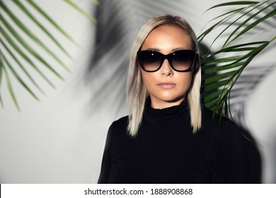 Close-up of woman with sunglasses with tropical palm leaves