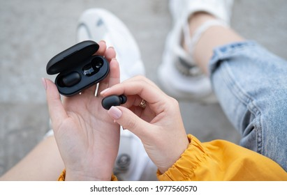 close-up of a woman taking out a black wireless earbud from his charging box. Female hands touching a portable gadget headphones
