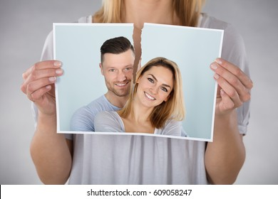 Close-up Of Woman Tearing Photo Of Smiling Couple