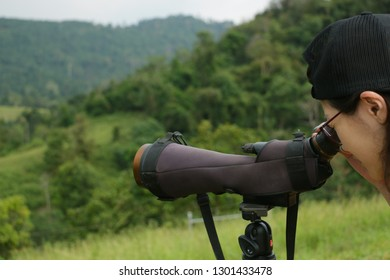 Close-up of a woman use binocular at the mountain for shedding animals in the green forest; soft focus.