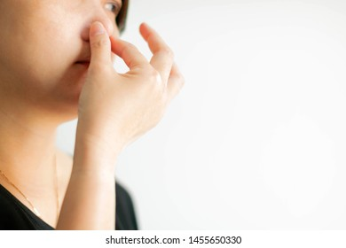 Close-up of woman use thumb and forefinger pinch her nose when scent bad smell; or getting air pollution on white background with copy space. concept of effect from pollution, health care and medical.