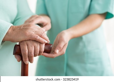 Close-up of woman using cane assisted by physiotherapist
