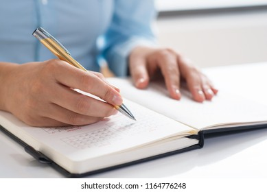 Closeup of woman using diary and scheduling. Entrepreneur sitting at desk. Planning concept. Cropped view.
