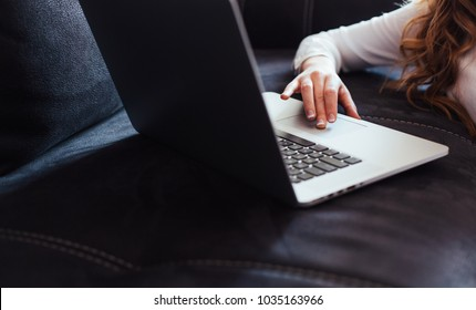 Closeup of woman using laptop on black sofa