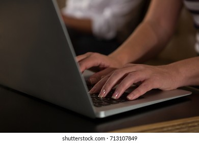 Close-up of woman using laptop in restaurant