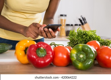 Close-up Of A Woman Using Mobile Phone With Vegetables In Kitchen