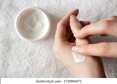 Close-up woman using moisturizer. Cream or body lotion on female hand in bathroom towel background, indoors. Daily skincare routine, top view