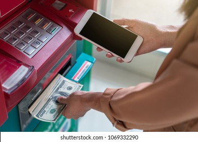 Closeup woman using the smart mobile phone for withdrawing the cash in front of the ATM, business Automatic Teller Machine concept