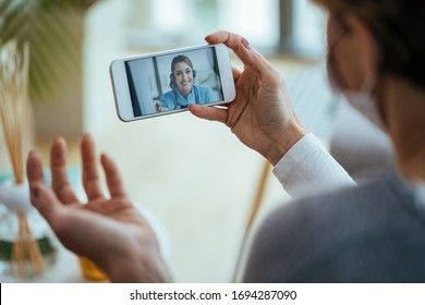 Close-up of woman using smart phone and having video call with healthcare worker during virus pandemic.