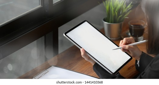 Close-up of woman using tablet with pencil while working at office