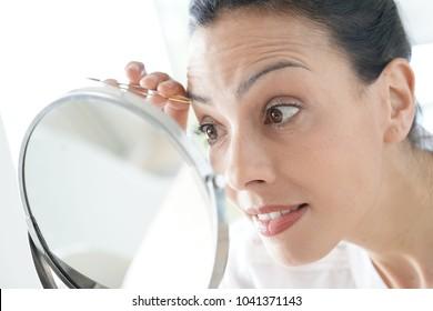 Closeup of woman using tweezers in front of mirror