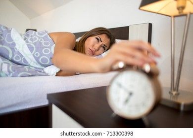 Closeup of a woman waking up in the morning reaching for the alarm clock to turn it off