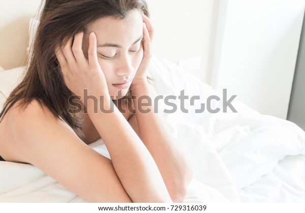 Closeup woman waking up with sore head on bed, health care and medical concept, selective focus
