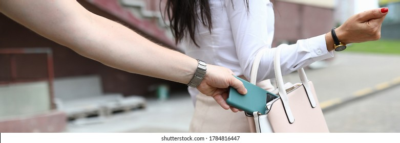 Close-up of woman walking on street. Man steal smartphone from females bag. Lady and street thief. Sad and problematic situation. Lost mobile phone concept