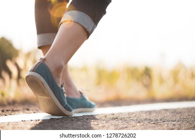 Closeup woman walking towards on the road side. Step concept.