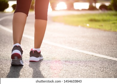 Closeup woman walking towards on the road side. Step, walk and outdoor exercise activities concept.