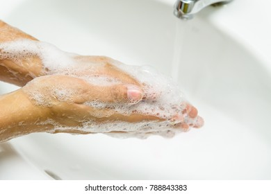 Closeup woman washing hands with soap under the faucet with water  in the bathroom.
