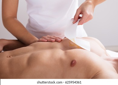 Close-up Of A Woman Waxing Man's Chest With Wax Strip