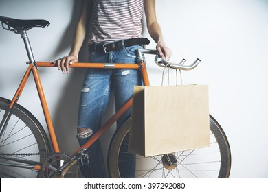 Closeup of woman wearing blue jeans and standing with vintage orange bike and blank paper package, mock-up of craft shopping bag with handles
