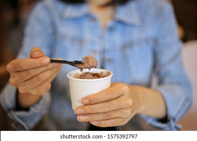 Closeup of woman wearing jean jacket left hand holding a takeaway white cup of homemade chocolate ice cream right hand holding small spoon with chocolate ice cream. flavour dessert snack gelato dairy
