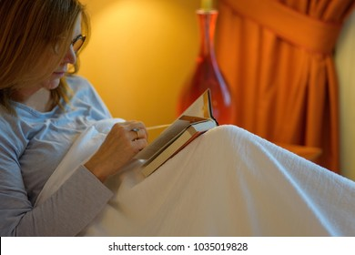 closeup of a woman wearing reading glasses reading a small book in bed at night