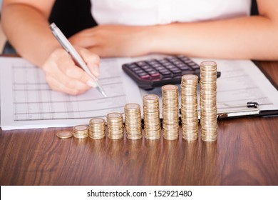 Close-up Of Woman At Work In Front Of Coin Graph