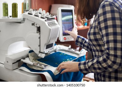 Close-up of woman working on modern computerized specially engineered embroidery machine with multi-needle fixed embroidery head creating green floral pattern on bright blue textile detail.