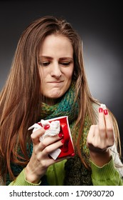 Closeup of a woman wrapped up in a scarf and holding a cup of hot tea expressing disgust to some drugs she is holding over gray background