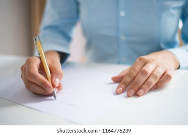 Closeup of woman writing on sheet of paper. Paper sheet lying on desk. Application concept. Cropped front view.
