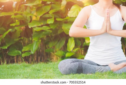 Closeup woman yoga with lotus hands in soft focus background with nature surrounding. Concept of healthy lifestyle and relaxation.