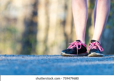 Close-up of woman's black running shoes with pink laces on nature jogging trail
