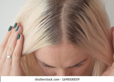 Closeup of a woman's blond head with parted hair regrown roots. Haircare, making new hairdo, hair therapy concept
